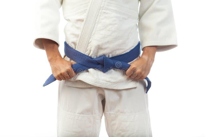 一个人的特写镜头一件白色和服的柔道的,栓蓝色 库存照片