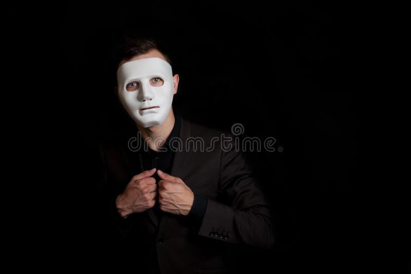 一个人的画象一个白色面具的在黑背景 拿着夹克的手 免版税库存照片