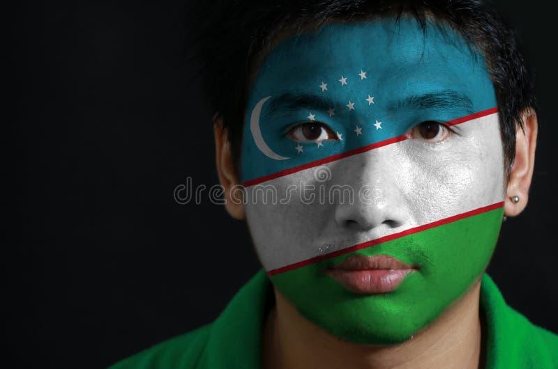 一个人的画象有乌兹别克斯坦的旗子的在他的在黑背景的面孔绘了 库存图片