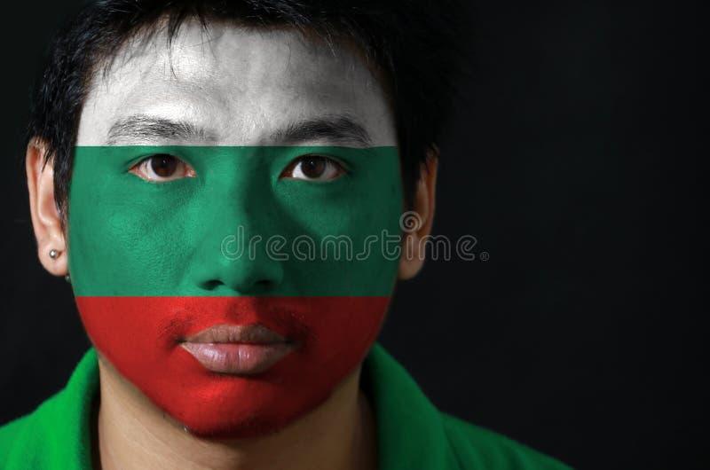 一个人的画象有保加利亚的旗子的在他的在黑背景的面孔绘了 库存图片