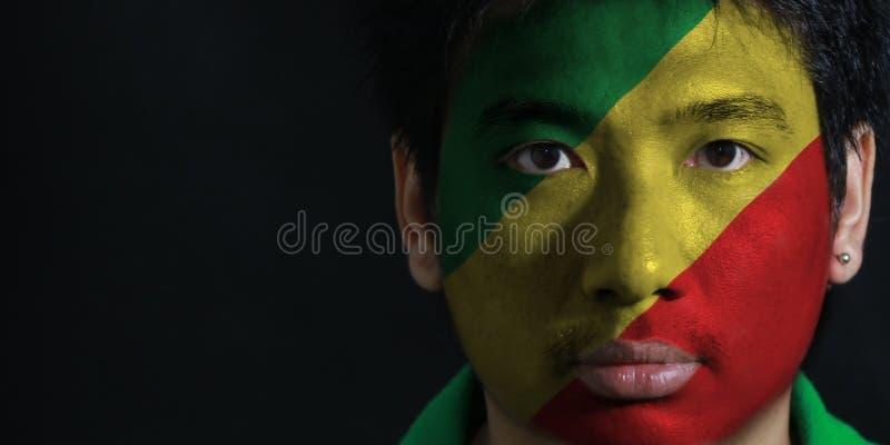 一个人的画象有刚果的旗子的在他的在黑背景的面孔绘了 免版税库存照片