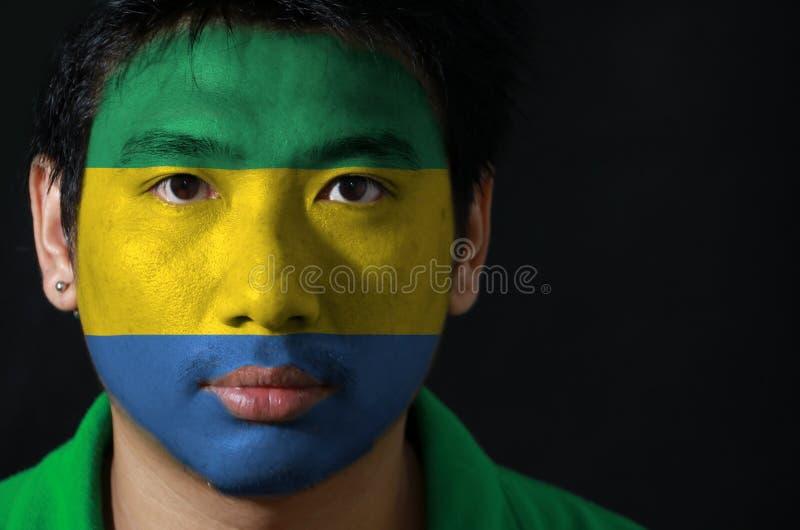 一个人的画象有加蓬的旗子的在他的在黑背景的面孔绘了 库存图片