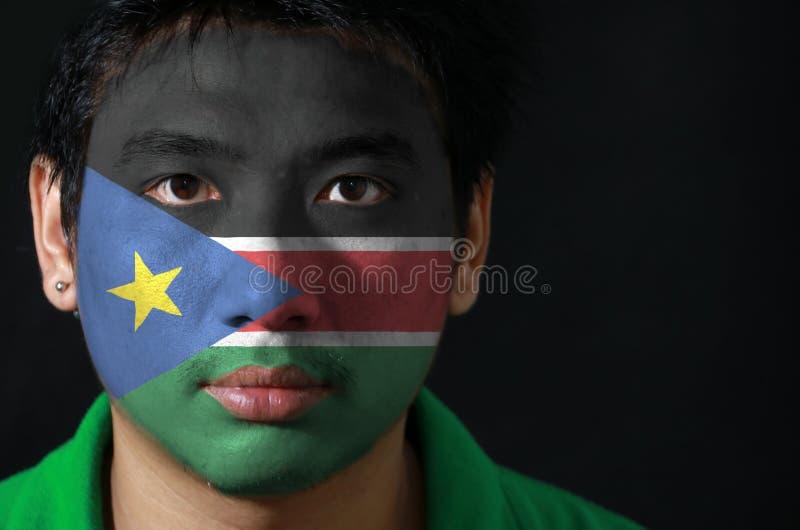 一个人的画象有南苏丹的旗子的在他的在黑背景的面孔绘了 库存照片