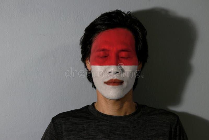 一个人的画象有印度尼西亚的旗子的在他的面孔和接近的眼睛绘了与黑阴影在灰色背景 库存照片