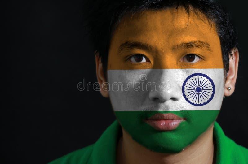 一个人的画象有印度的旗子的在他的在黑背景的面孔绘了 免版税库存照片