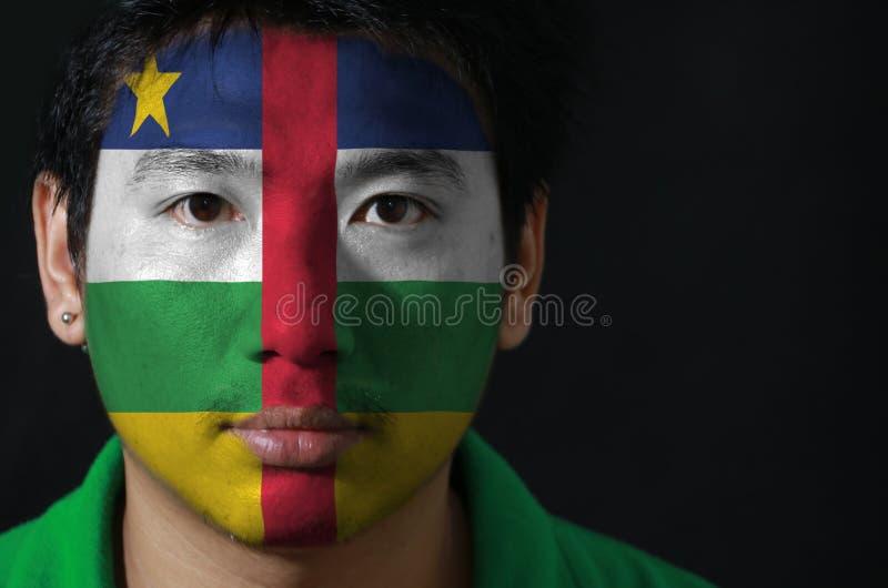 一个人的画象有在他的在黑背景的面孔绘的旗子的中非 免版税库存图片