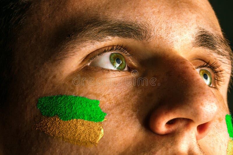 一个人的画象有在他绘的巴西的旗子的面孔 库存图片