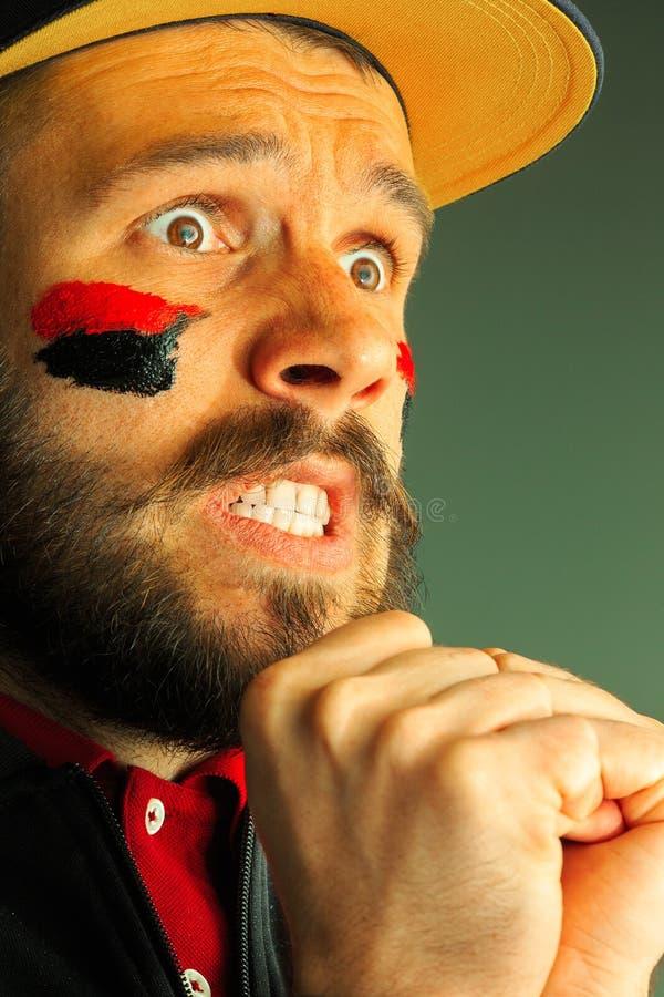 一个人的画象有在他绘的德国的旗子的面孔 库存图片
