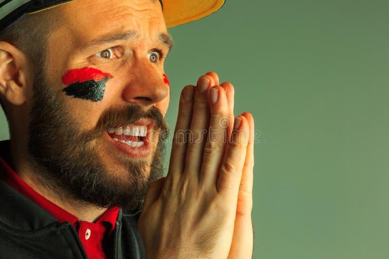 一个人的画象有在他绘的德国的旗子的面孔 免版税库存照片