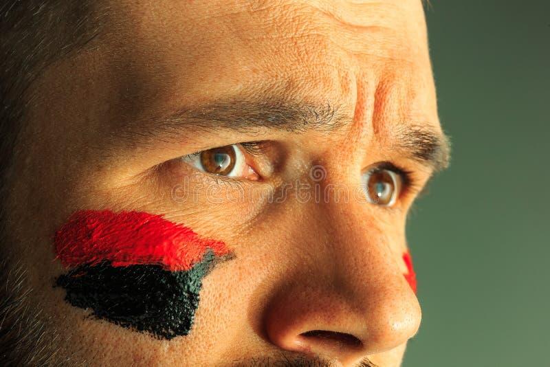 一个人的画象有在他绘的德国的旗子的面孔 免版税图库摄影
