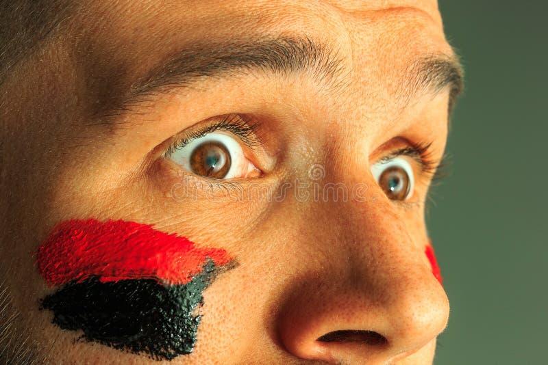 一个人的画象有在他绘的德国的旗子的面孔 免版税库存图片