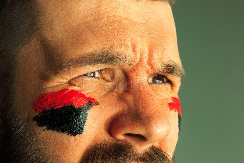 一个人的画象有在他绘的德国的旗子的面孔 库存照片
