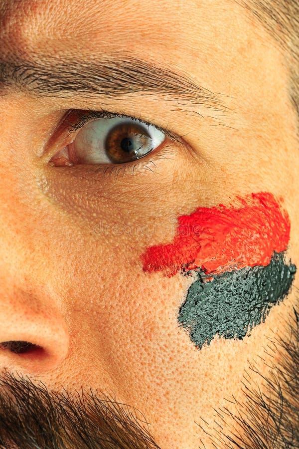 一个人的画象有在他绘的德国的旗子的面孔 图库摄影