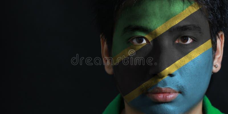 一个人的画象有坦桑尼亚的旗子的在他的在黑背景的面孔绘了 图库摄影