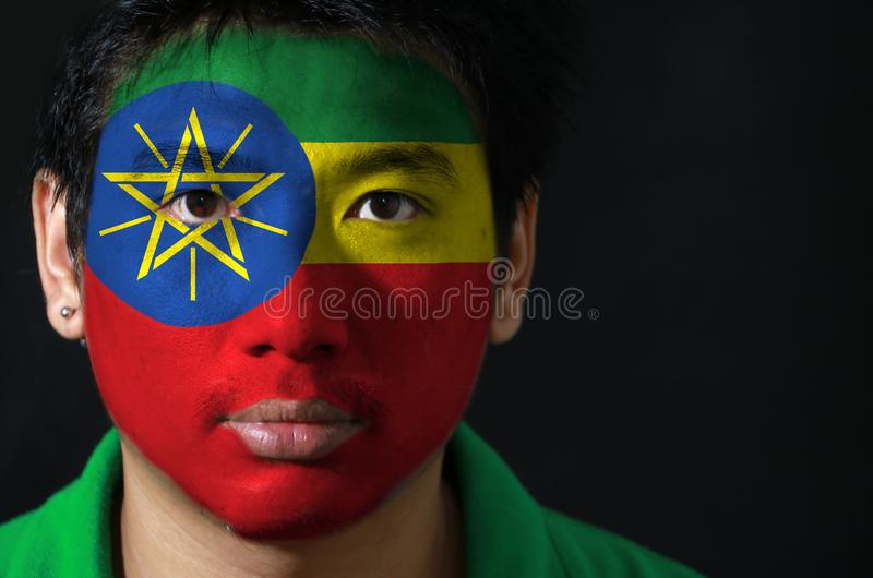 一个人的画象有埃塞俄比亚的旗子的在他的在黑背景的面孔绘了 库存照片
