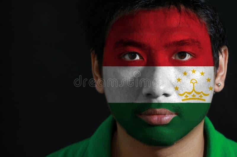 一个人的画象有塔吉克斯坦的旗子的在他的在黑背景的面孔绘了 免版税库存照片