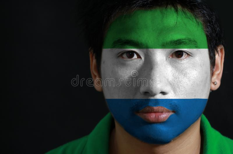 一个人的画象有塞拉利昂的旗子的在他的在黑背景的面孔绘了 免版税库存照片