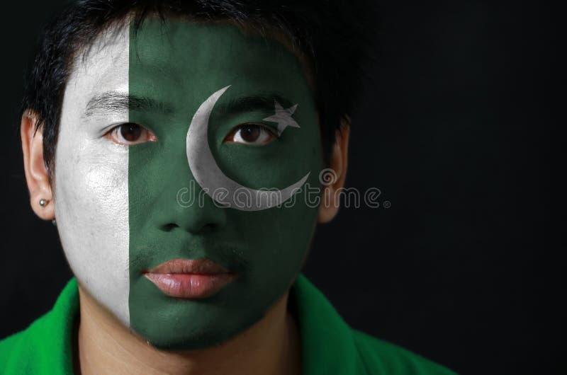 一个人的画象有巴基斯坦的旗子的在他的在黑背景的面孔绘了 库存照片