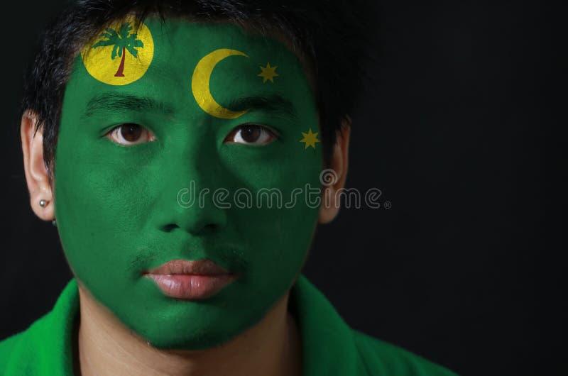 一个人的画象有椰树Keeling海岛的旗子的在他的在黑背景的面孔绘了 库存图片