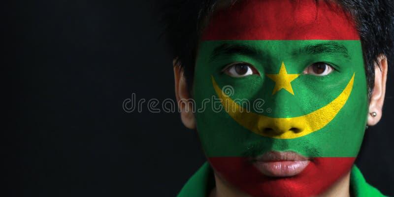 一个人的画象有毛里塔尼亚的旗子的在他的在黑背景的面孔绘了 免版税库存图片