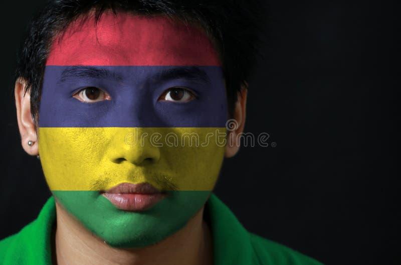 一个人的画象有毛里求斯的旗子的在他的在黑背景的面孔绘了 免版税库存图片