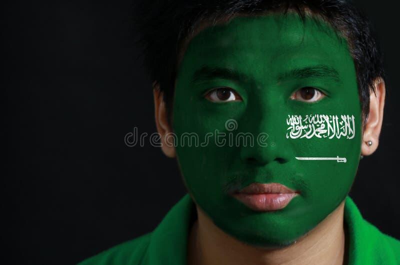 一个人的画象有沙特阿拉伯的旗子的在他的在黑背景的面孔绘了 库存照片