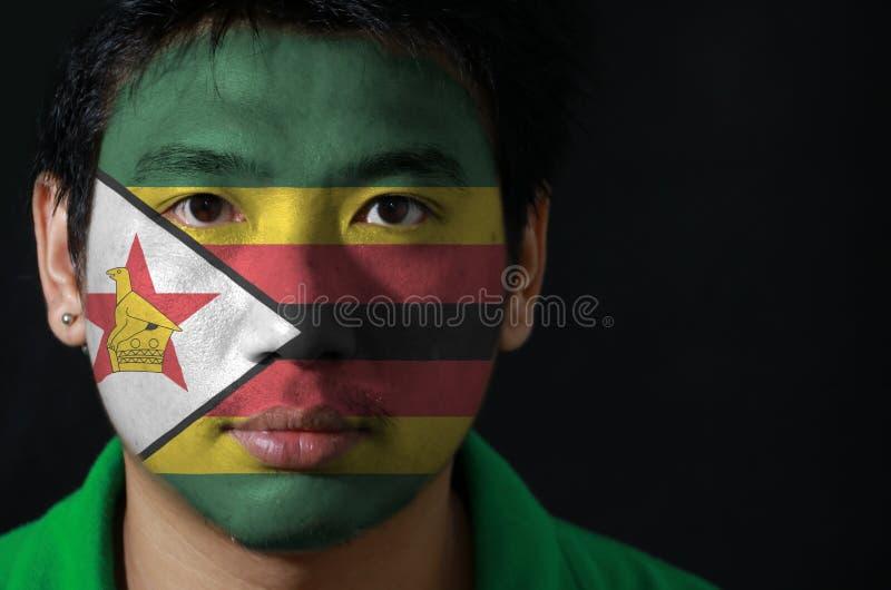 一个人的画象有津巴布韦的旗子的在他的在黑背景的面孔绘了 免版税库存照片