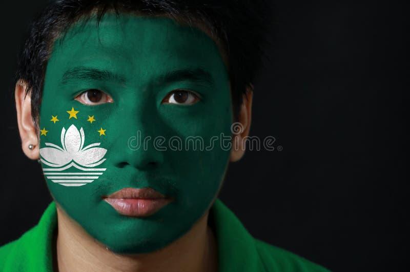 一个人的画象有澳门的旗子的在他的在黑背景的面孔绘了 库存图片