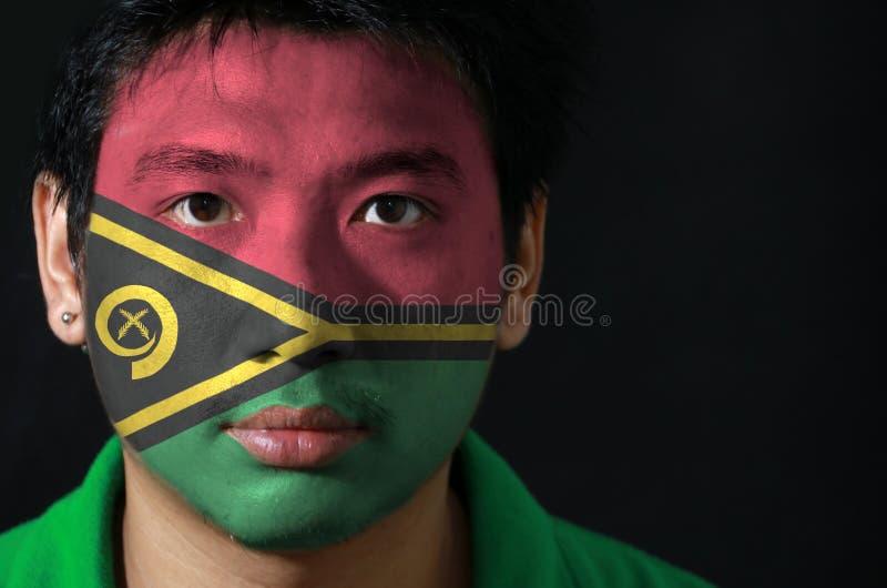 一个人的画象有瓦努阿图的旗子的在他的在黑背景的面孔绘了 免版税库存照片