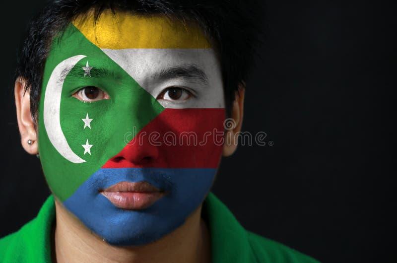 一个人的画象有科摩罗的旗子的在他的在黑背景的面孔绘了 图库摄影