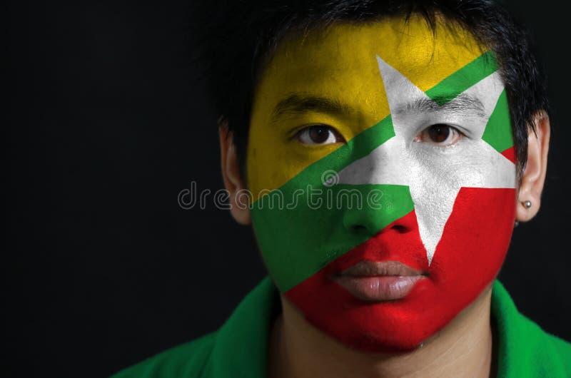 一个人的画象有缅甸的旗子的在他的在黑背景的面孔绘了 免版税库存图片