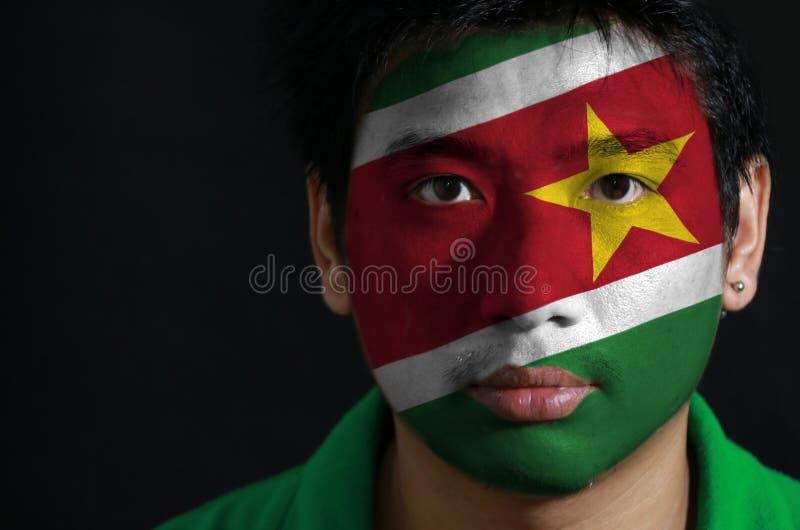 一个人的画象有苏里南的旗子的在他的在黑背景的面孔绘了 库存照片
