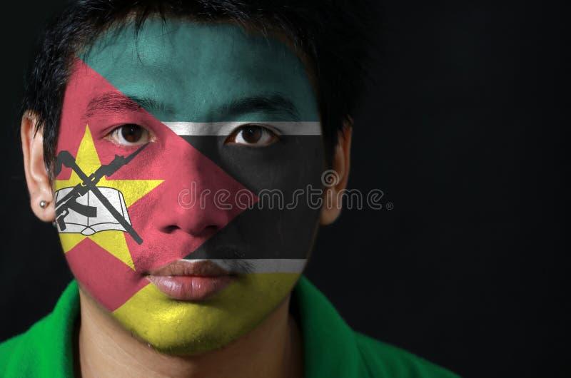 一个人的画象有莫桑比克的旗子的在他的在黑背景的面孔绘了 免版税库存图片