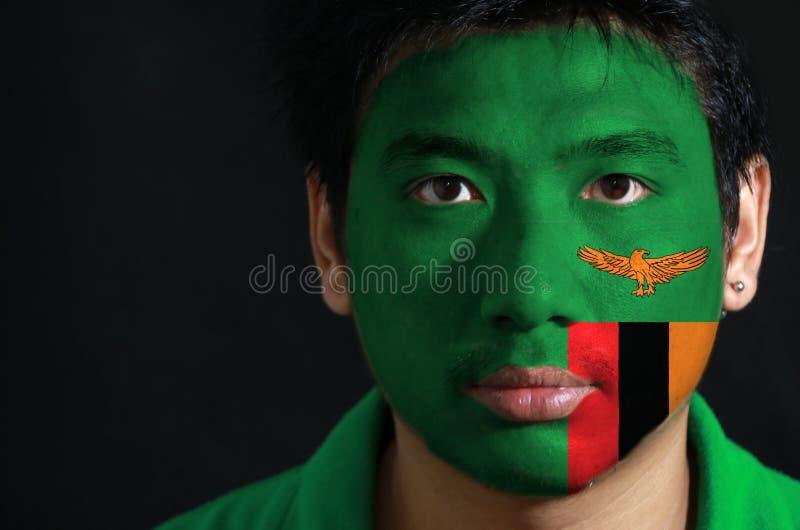一个人的画象有赞比亚的旗子的在他的在黑背景的面孔绘了 免版税图库摄影