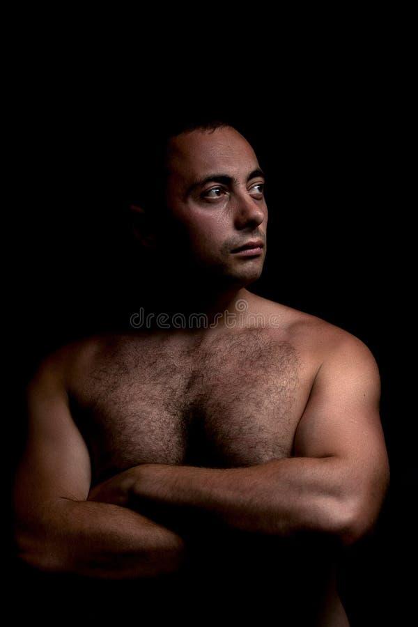 一个人的画象有赤裸躯干的在一低调在阴影 图库摄影