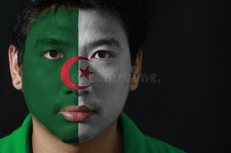 一个人的画象有阿尔及利亚的旗子的在他的在黑背景的面孔绘了 免版税库存图片