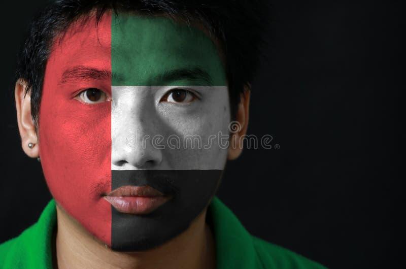 一个人的画象有阿拉伯联合酋长国的旗子的在他的在黑背景的面孔绘了 免版税图库摄影