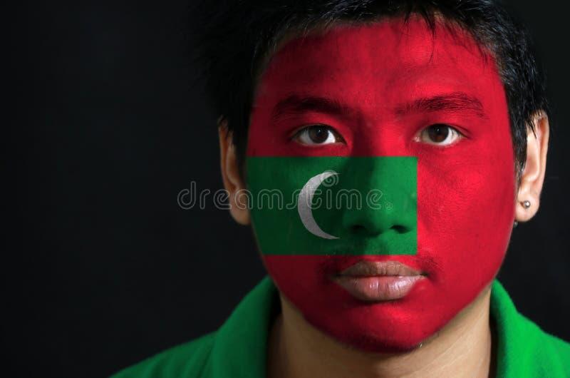 一个人的画象有马尔代夫的旗子的在他的在黑背景的面孔绘了 库存照片