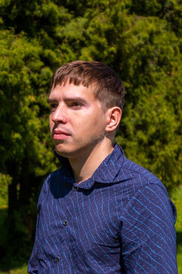 一个人的画象蓝色衬衣身分的外部在公园 免版税库存图片