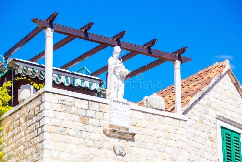 一个人的白色雕象用在一个房子的屋顶的一根发光的铁棍子在分裂,克罗地亚老镇的中心  免版税库存照片
