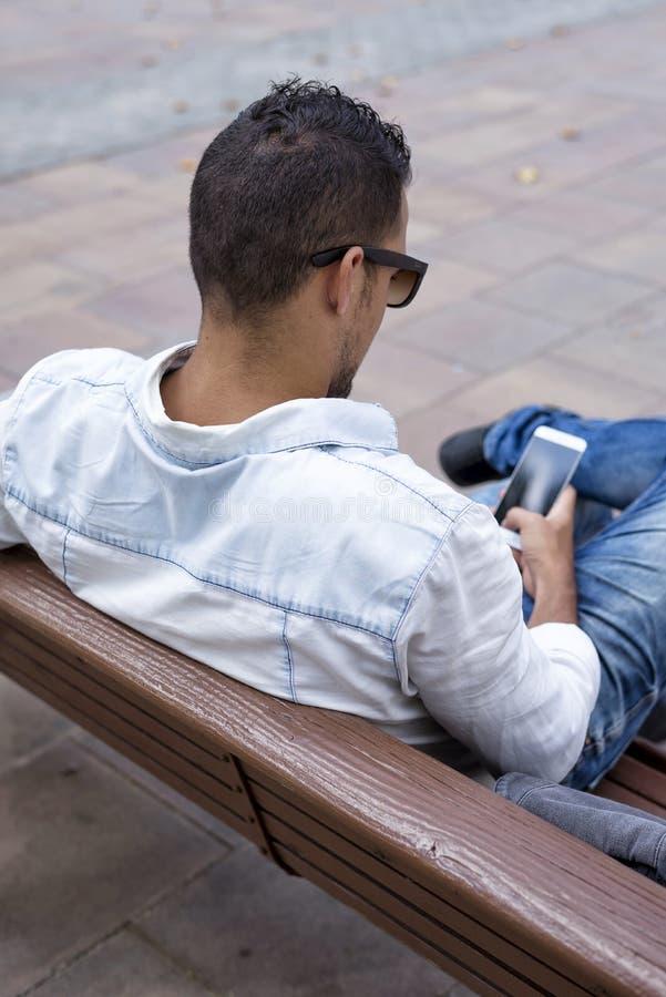 一个人的背面图使用智能手机的,当坐长凳户外时 图库摄影