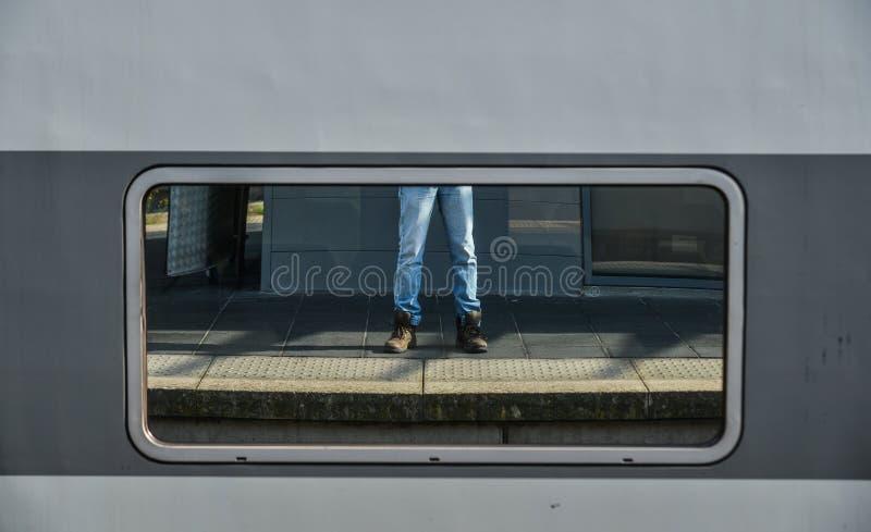 一个人的腿斜纹布和运动鞋的 库存照片
