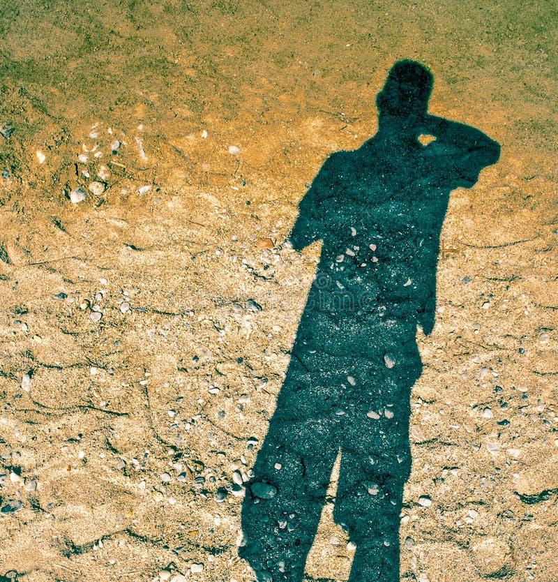 一个人的阴影沙子的,太阳在后面,在吱吱声的阴影浮游物发光 库存照片