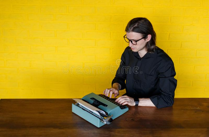 一个人的顶视图镜片的,在黑衬衣,供以座位在桌上,运作在一台打字机,在yello墙壁 库存图片