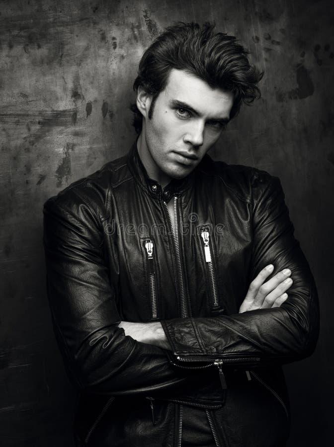 一个人的黑白画象黑皮夹克的在墙壁附近 库存图片