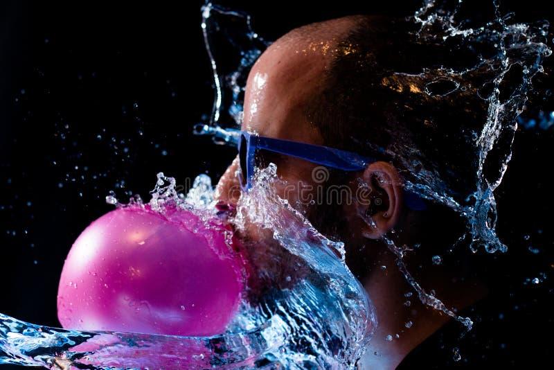 一个人的画象以太阳镜口香糖和是在面孔的被投掷的水 免版税库存照片