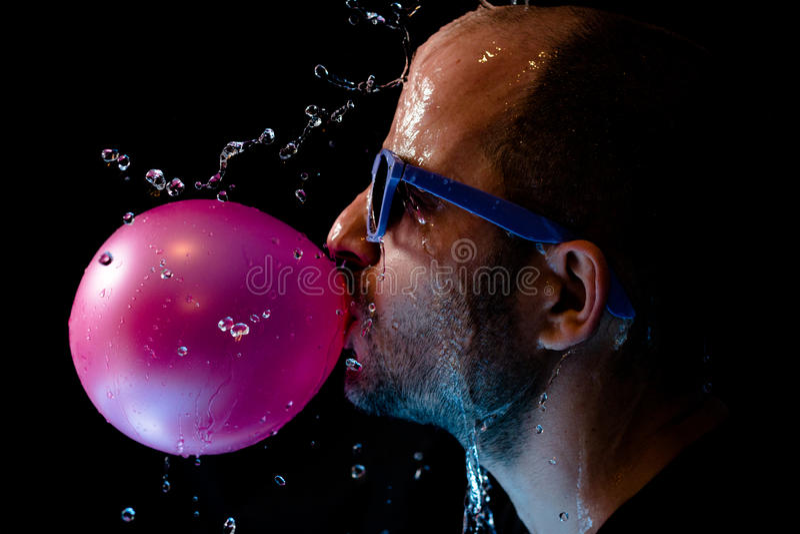 一个人的画象以太阳镜口香糖和是在面孔的被投掷的水 图库摄影