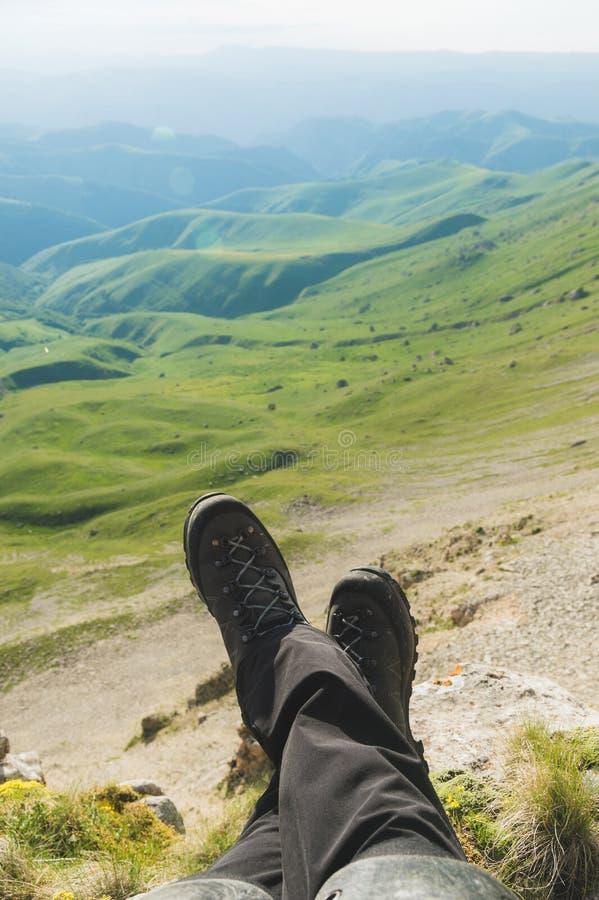 一个人的first-person图POV坐在高峭壁边缘并且享受风景 迁徙广角的人脚 图库摄影
