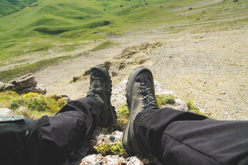 一个人的first-person图POV坐在高峭壁边缘并且享受风景 迁徙广角的人脚 库存图片