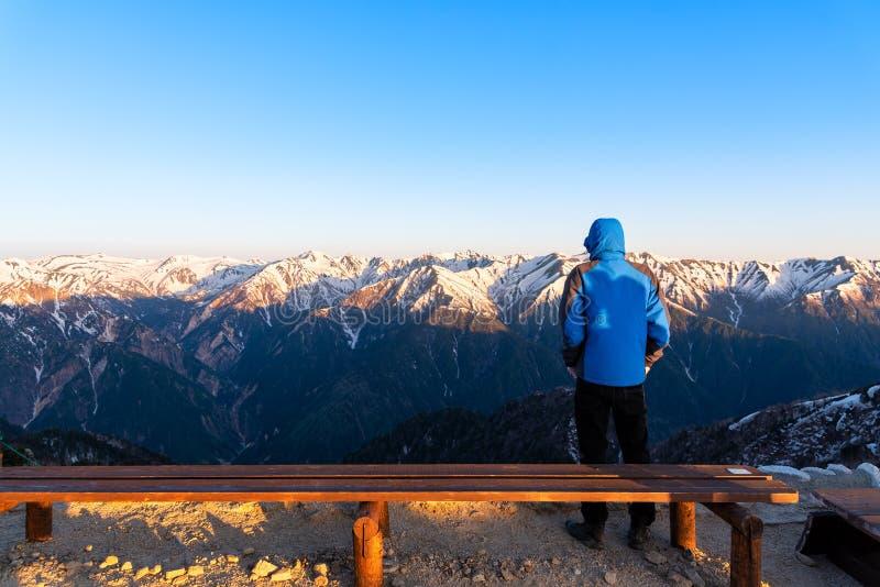 一个人看登上Tsubakuro达克风景在日落 雪酷寒北风日本阿尔卑斯Chubu-Sangaku公园的山脉 免版税库存照片
